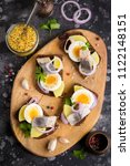 Stock photo sandwich on bread with herring potatoes egg onion tasty appetizer with mustard on the board 1122148151