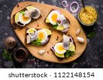 Stock photo sandwich on bread with herring potatoes egg onion tasty appetizer with mustard on the board 1122148154