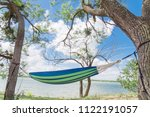 Small photo of Empty green hammock in shade tree shades at lakeside park in Grand Prairie, Texas, USA. Vacation, relaxation and enjoy the beauty of the nature. Wanderlust and travel concept, cloud blue sky