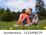 kissing couple sitting in green ... | Shutterstock . vector #1122498179