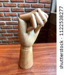 Small photo of Right Stranglehold wooden hand on a brick wall background