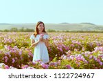 Stock photo beautiful young woman posing near roses in a garden 1122724967