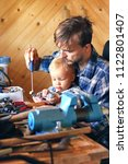 father and son in workshop... | Shutterstock . vector #1122801407