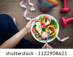 sporty woman holding salad dish ...   Shutterstock . vector #1122908621