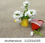 Bouquet from white phloxes in a yellow watering-can and red heart on a canvas table - stock photo