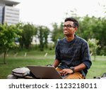 a student from india sits with... | Shutterstock . vector #1123218011