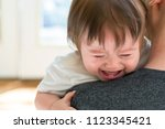 Small photo of Upset toddler boy crying on his father's shoulder in his house