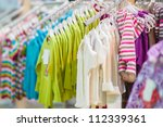 Sweaters and blouses on stands in kids mall - stock photo