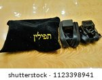 """Small photo of Moscow, Russia - June 28, 2018 - A set of tefillin with verses from Torah written on them and a pouch saying """"tefillin"""" in Hebrew on it"""