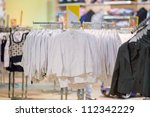 Stand with white blouses in kids mall - stock photo