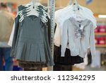 Blouses, jumpers and dresses in kids mall - stock photo