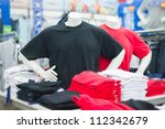 Mannequins in black and red t-shirts on table in mall - stock photo