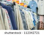 Variety os t-shirts and trousers on stands in supermarket - stock photo