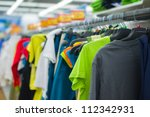 Variety of color T-shirts on stands in supermarket - stock photo