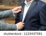 tailor measures a man | Shutterstock . vector #1123437581