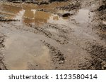 visible tire tracks in the mud. ... | Shutterstock . vector #1123580414