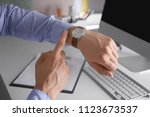young man checking time on his... | Shutterstock . vector #1123673537