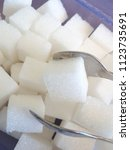 Small photo of white sugar cubes with a sugar tongs