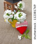 Romantic bouquet from white phloxes in a yellow watering-can and red heart on a canvas table - stock photo