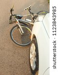 Small photo of a close-up of a bicycle caught under the wheels of a car. accident on the road, accident, traffic rules