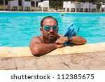 Man with flippers in the swimming pool - stock photo