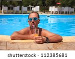 Man drinking juice in the swimming pool - stock photo