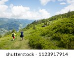 two hikers on a lush green high ... | Shutterstock . vector #1123917914