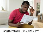 shocked sad african young man... | Shutterstock . vector #1124217494