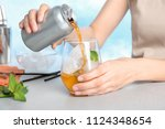 woman pouring drink from tin... | Shutterstock . vector #1124348654