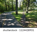Small photo of asphalt path or trail with shortcut path through the dirt and grass