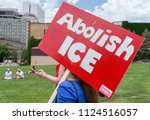 "Small photo of MINNEAPOLIS, MN/USA - JUNE 30, 2018: Unidentified individual carrying a sign saying ""Abolish Ice"" at the Families Belong Together march."