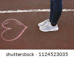 feet in shoes on asphalt  with...   Shutterstock . vector #1124523035