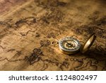 old gold compass on ancient map ... | Shutterstock . vector #1124802497