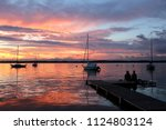 Amazing summer evening landscape with group of drifting yachts on a lake, two people on a wooden pier. Mendota during spectacular sunset. Bright sky reflects in the lake water.