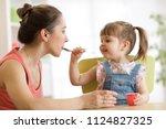 playful child girl spoon... | Shutterstock . vector #1124827325