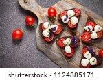 bruschetta with mozzarella and... | Shutterstock . vector #1124885171