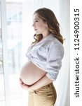 pregnant woman at window... | Shutterstock . vector #1124900315