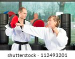 Small photo of People in a gym in martial arts training exercising Taekwondo, both have a black belt