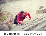 young man climbing on a stone... | Shutterstock . vector #1124974304