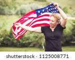 woman holding american flag in... | Shutterstock . vector #1125008771