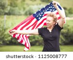woman holding american flag in... | Shutterstock . vector #1125008777