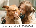 Stock photo girl kissing hugging dog pet cute adorable red dog friendly closeup closing eyes funny animals 1125010061