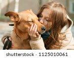 girl kissing hugging dog pet... | Shutterstock . vector #1125010061