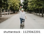 Stock photo  sweet middle aged woman playing with her nice brown spanish waterdog on a sunny summer day in a 1125062201