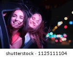 two girls are riding in car and ... | Shutterstock . vector #1125111104