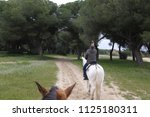 a man on a horseback is taking... | Shutterstock . vector #1125180311