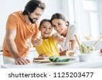 beautiful young family cooking... | Shutterstock . vector #1125203477