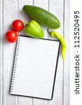blank recipe book with vegetable on kitchen table - stock photo