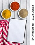 various colored spices with blank recipe book. studio shot. - stock photo