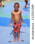 young boy in the water park water jet fountains - stock photo